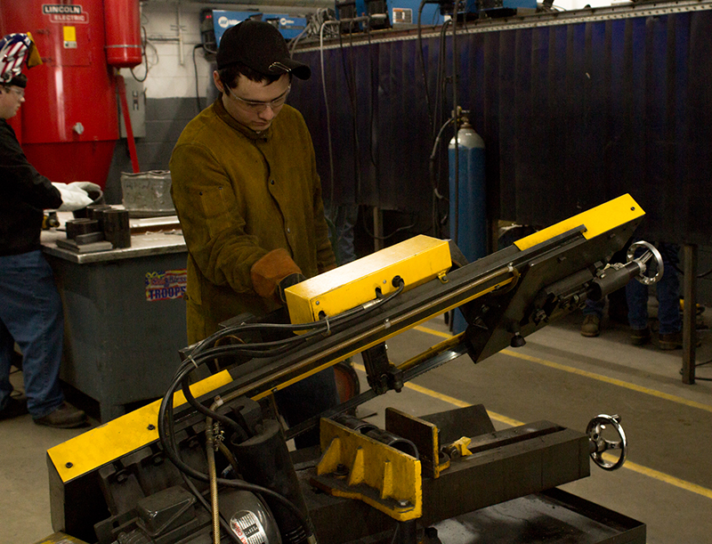 Student operating fabricating equipment